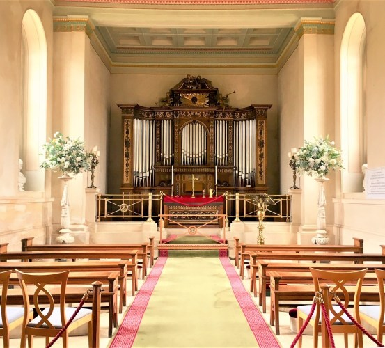 The inside of Bowood Chapel with pews and huge chamber organ