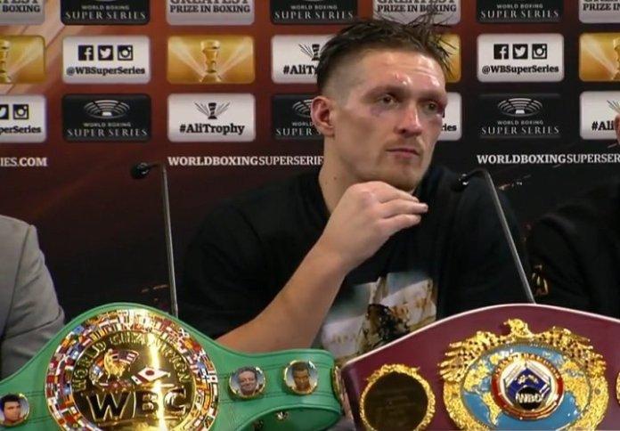 Usyk mit seinen beiden WM Gürteln vor sich bei der Pressekonferenz nach dem denkwürdigen Fight.