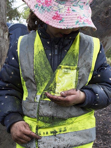 Child looking at millipede at Batman Park Kindergarten bush kinder