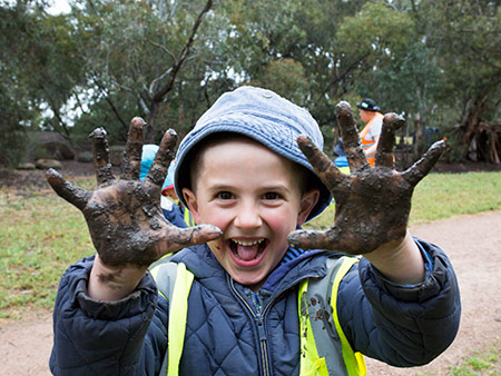 Child with muddy hands and gleeful face at Batman Park Bush Kindergarten.