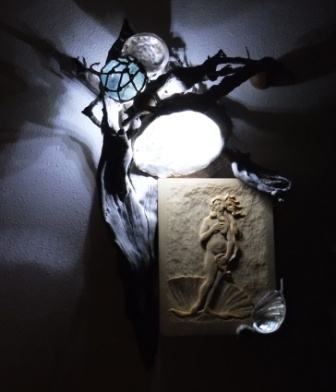 Venus wood carving mounted in driftwood with light