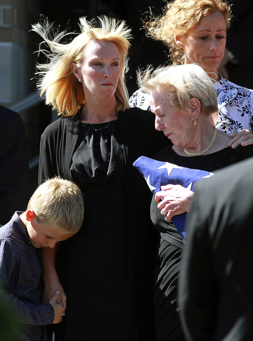 Winchester, MA - The family of Glen Doherty who was killed in Benghazi, including his mother Barbara Doherty holding the flag, sister Katie Quigley (center), and nephew Cam Quigley leave the church following the funeral.