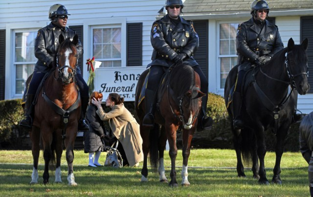 A women comforts a young girl as mounted police stand outside the wake for 6 year old Jesse Lewis, one of the 20 first graders shot and killed at Sandy Hook Elementary School, at Honan Funeral Home in Newtown, CT.