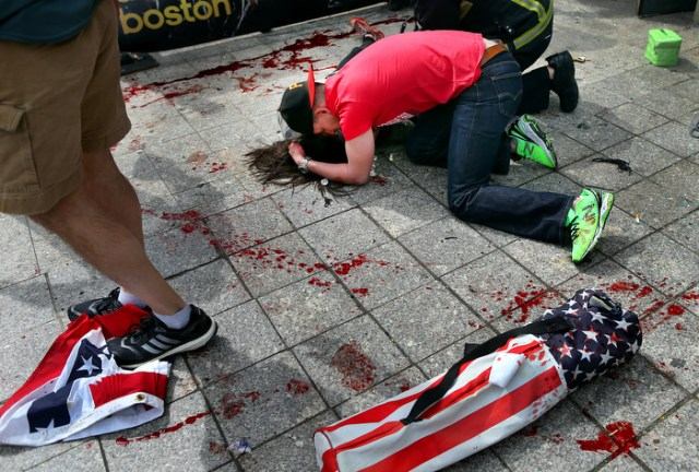Boston-4/15/13- Joe Duncan, a Marine comforts a woman who was hit by shrapnel from the first terrorist bomb on the sidewalk near he finish line of Boylston Street.