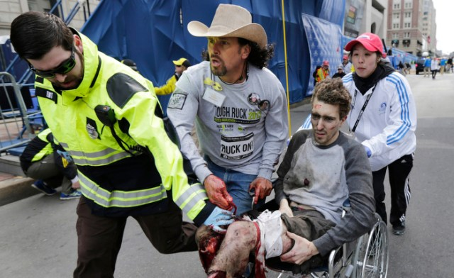Boston Marathon survivor Jeff Bauman is wheeled from the site of an explosion near the finish line of the Boston Marathon by medical volunteer Devin Wang, as bystander Carlos Arredondo and EMT Paul Mitchell keep Bauman from bleeding out, Monday April 15, 2013.