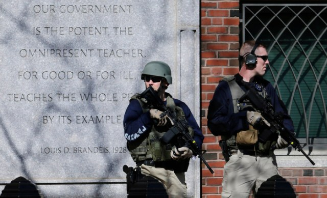 U.S. Marshals in tactical gear stand guard outside Boston's Moakley Federal Court House after if was evacuated, Wednesday, April 17, 2013. The building was evacuated amid conflicting reports that a suspect in the Boston Marathon bombing was in custody and about to be brought into the court house.