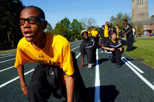 CJ Thomas, from the Maryland School for the Blind, leads his teammates in warm-ups for the 67th annual Eastern Athletic Association for the Blind track and field tournament hosted at the Perkins School for the Blind in Watertown, Massachusetts May 18, 2013.