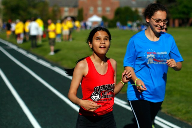 Britini Witter (L), from Overbrook School for the Blind, and her guide runner Andrea Stein compete in the girls' mile at the 67th annual Eastern Athletic Association for the Blind track and field tournament hosted at the Perkins School for the Blind in Watertown, Massachusetts May 18, 2013.