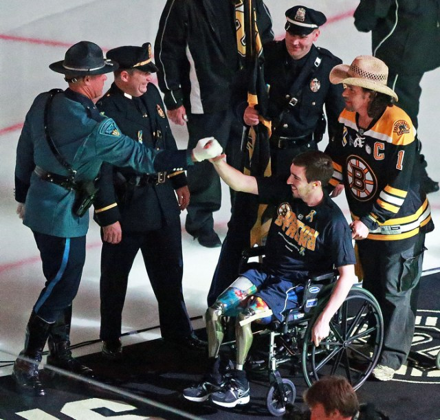 Boston Marathon bombing victim Jeff Bauman and Carlos Arredondo, the man who wheeled him to medical attention after he lost both legs in the blast are greeted by first responders as they leave the ice following a pre game flag waving. The Boston Bruins hosted the Chicago Blackhawks for Game Six of the Stanley Cup Finals at the TD Garden.