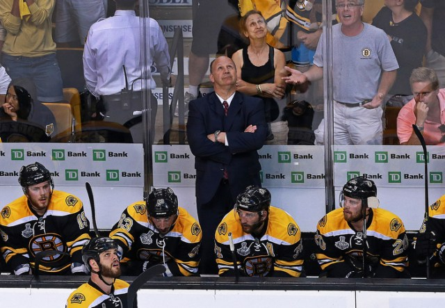 As the Blackhawks celebrate winning the Stanley Cup,  Bruins head coach Claude Julien, players and fans glumly watch the replay of the game winning Chicago goal.
