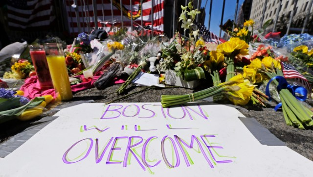 Flowers and signs adorn a barrier at Boylston Street near the of finish line of Monday's Boston Marathon explosions, which killed at least three and injured more than 140, in Boston, Wednesday, April 17, 2013.