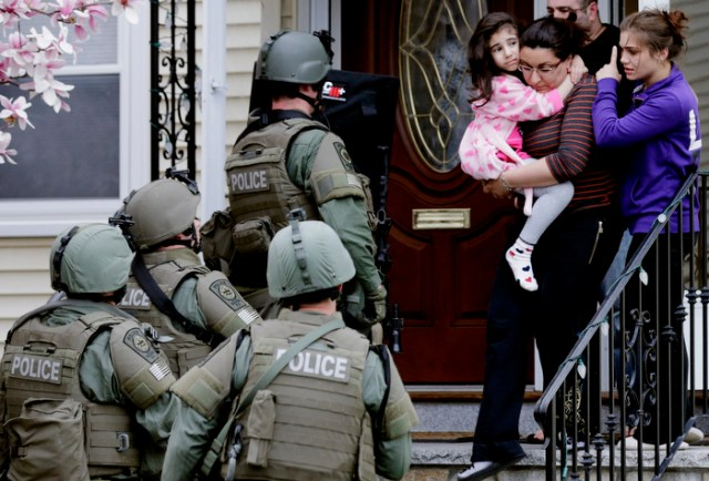 A woman carries a girl from their home as a SWAT team searching for a suspect in the Boston Marathon bombings enters the building in Watertown, Mass., Friday, April 19, 2013.