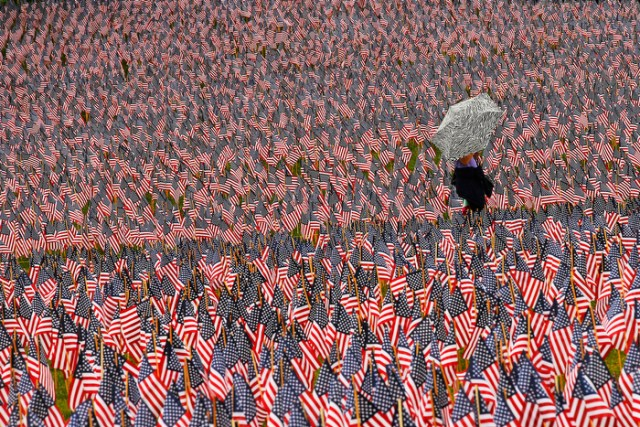 A pedestrian carrying an umbrella walks through a Memorial Day display of United States flags on the Boston Common in Boston, Massachusetts May 23, 2013.