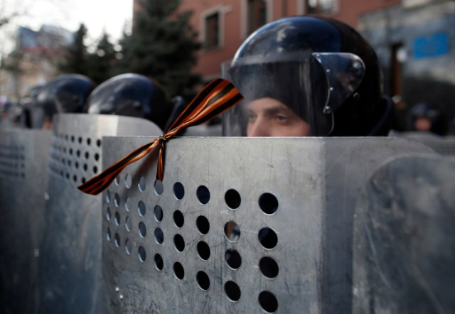 Donetsk, Ukraine-- 03/16/2014-- A Ukrainian police officer in riot gear stands with an orange and black ribbon of St. George meant as a Russian symbol of World War II commemoration tied to his shield after a Pro-Russian protester tied it on during a protest outside of the Donetsk Prosecutors Building in Donetsk, Ukraine March 15, 2014.