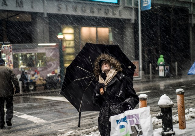 A woman looks up at the skyline and falling snow in New York, New York, USA 03 February 2014. The New York City area is expecting up to eight inches (21cm) according to the National Weather Service through the 24 hours.