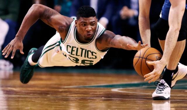 Boston Celtics guard Marcus Smart dives as Minnesota Timberwolves forward Robbie Hummel picks up the loose ball at the Boston Garden.