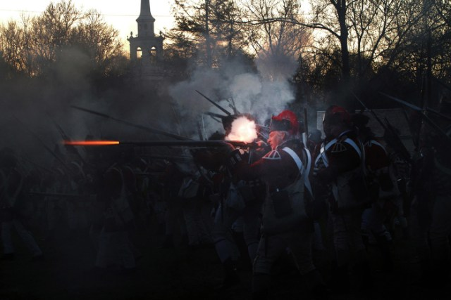 British Army regulars fire on the militia during the Revolutionary War battle reenactment on Patriots Day in Lexington, Mass., Monday, April 21, 2014.