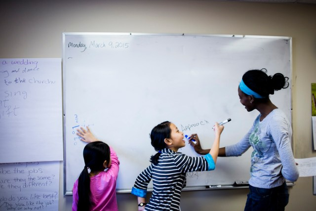 A Karen refugee from Myanmar, Su Mei, 11, and a volunteer (right) from the University of Massachusetts playspelling games on the white board during an after school homework help program.