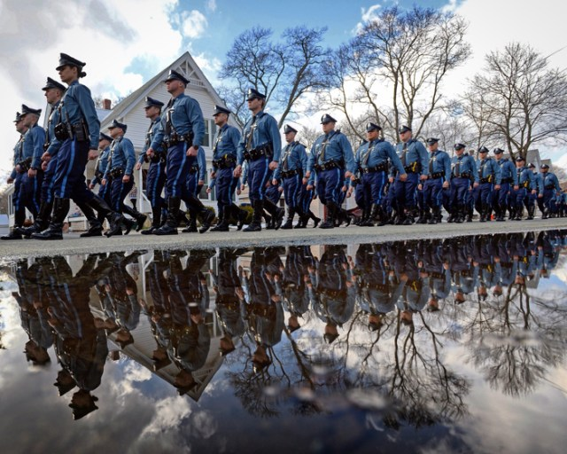 Members of the Massachusetts State Police march in formation as they participate in a walk-by at the the wake for Trooper Thomas Clardy in Hudson on Monday, March 21, 2016. Clardy was killed in the line of duty as a result of an accident on the Massachusetts Turnpike