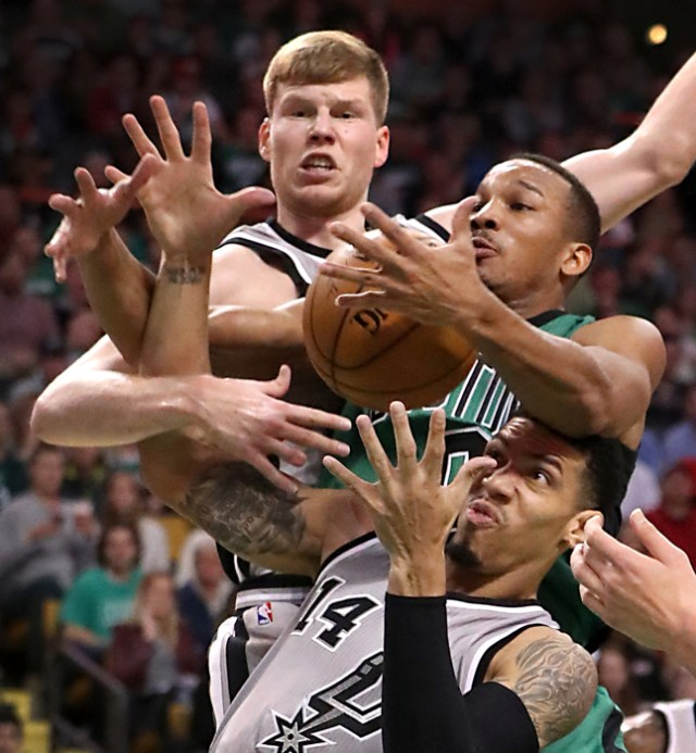 Boston MA 11/25/16 Boston Celtics Avery Bradley battles for a loose ball with San Antonio Spurs Davis Bertans (top) and Danny Green during fourth quarter action at the TD Garden.