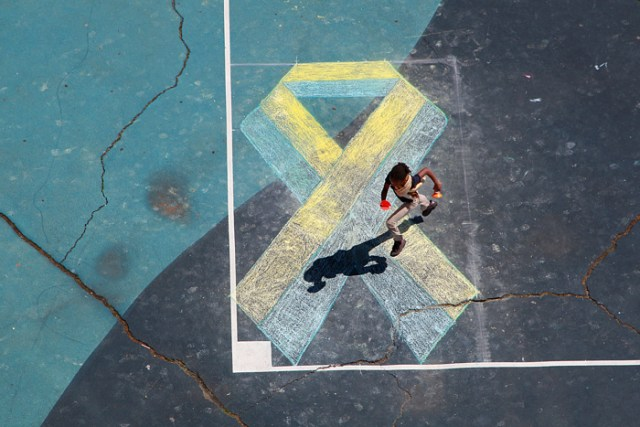 A student runs over the chalk Boston Strong ribbon created by the students  at the Oliver Hazard Perry School in South Boston to mark the third anniversary of the Boston Marathon Bombing.