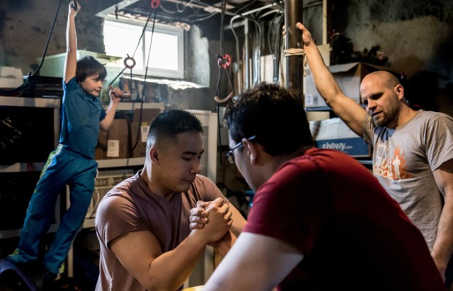 Alex Pei (center left) practices arm wrestling with a fellow competitor as Joshua Grant (right) and his son Callum Grant, 6, look on in Allston, Mass., on April, 24, 2016.