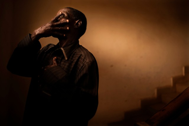 In north-central Nigeria, a portrait of an HIV- positive clinic worker shields his face from the camera because of the widespread stigma and shame of AIDS, on June 14, 2017.