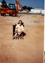 """Mom, sitting in the little bucket of a backhoe during construction fo the """"new"""" building"""