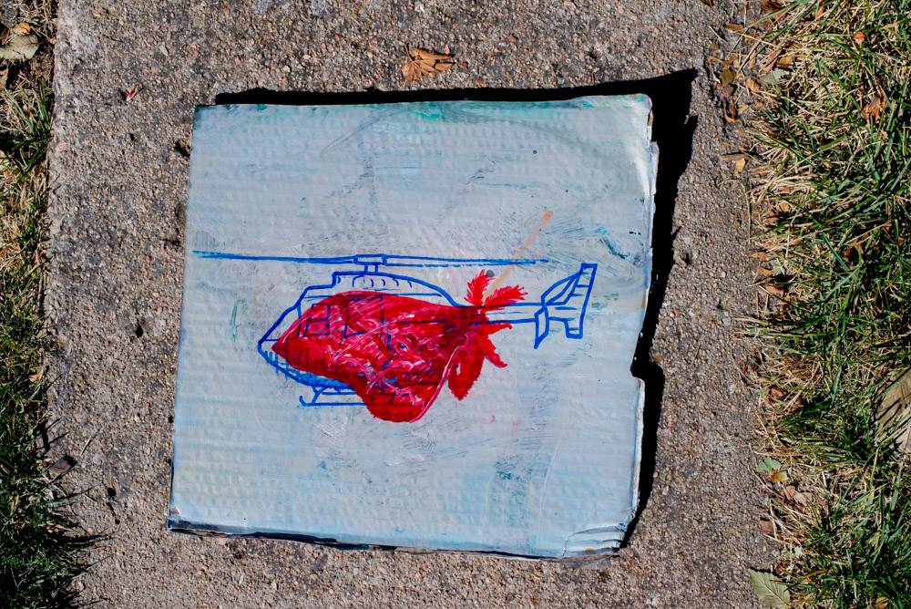 a painting of a moth in red overlapping a painting of a helicopter in blue on cardboard