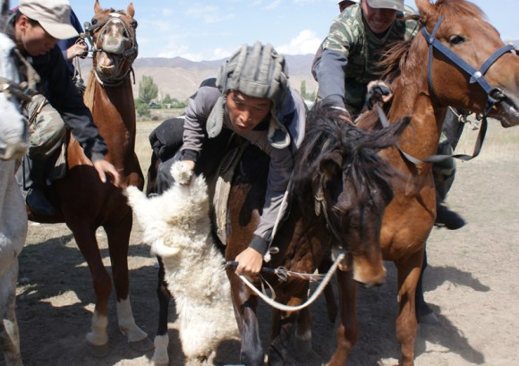 Participants fight over the dead goat in a buz kashi game, Tajikistan by Maximum Exposure Productions