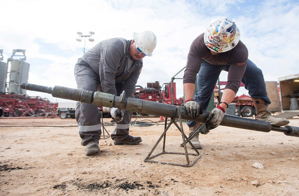 Arklatex Energy Services field hands take apart the perforating gun system while on location, Monday, Aug. 22, 2016, in Andrews, Texas.