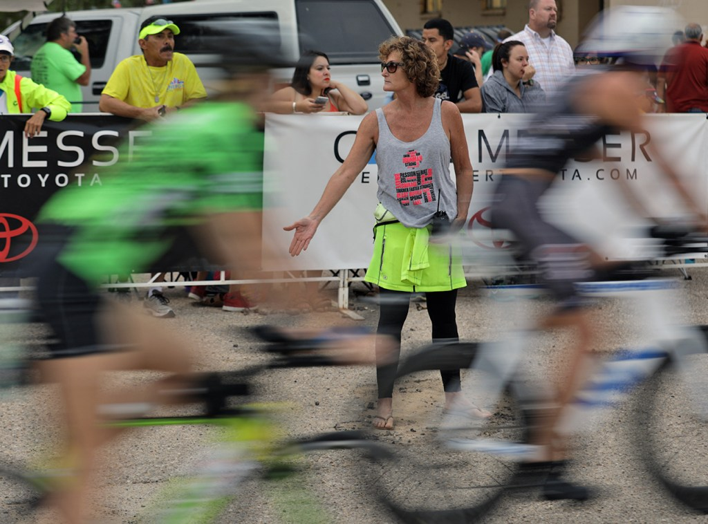 Marti Greer, the race director, moves cyclists away from sand in the road during the Ironman 70.3 Buffalo Springs Lake, Sunday, June 25, 2017, at Buffalo Springs Lake in Buffalo Springs, Texas. (Brad Tollefson/A-J Media)