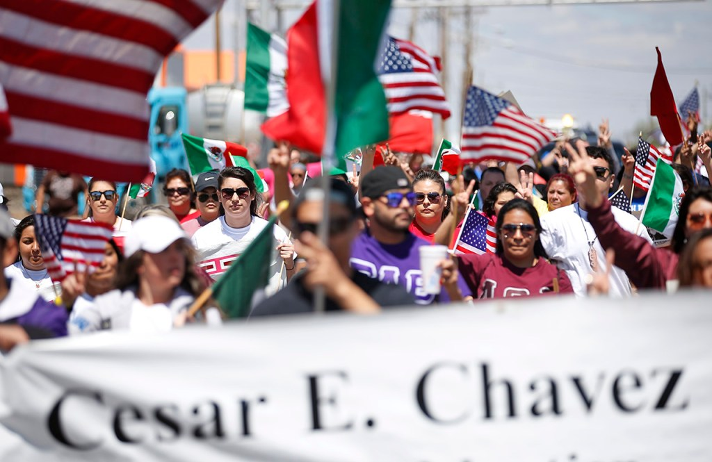Marchers walk down University Avenue during the Cesar Chavez march on Saturday, April 9, 2016, at Lubbock, Texas.