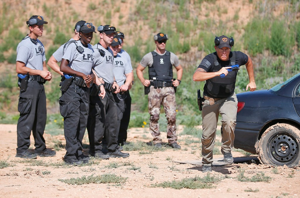 John Wilhelm, a police instructor, demonstrates running to a second car while explaining a close quarter battle during training at the Lubbock Police academy Thursday, Aug. 10, 2017, at the Lubbock Police Shooting Range in Lubbock, Texas. The class graduates from the academy on August 25.