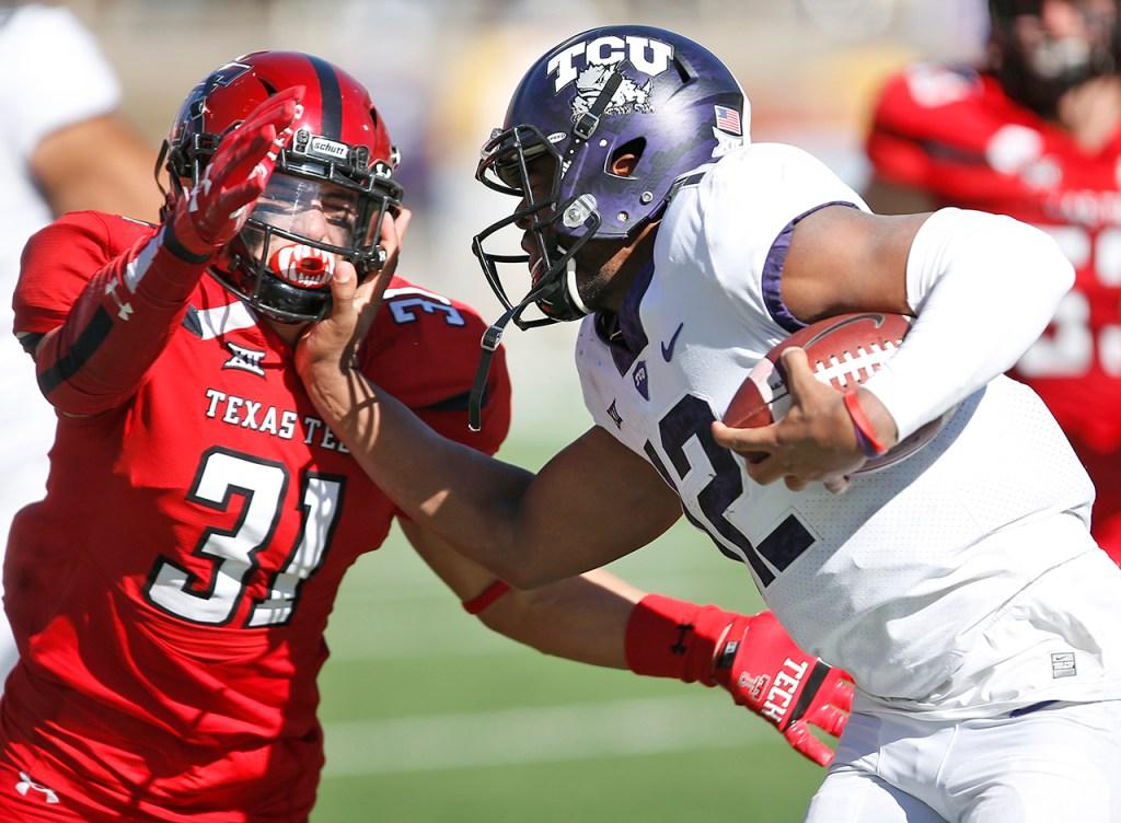 TCU's Shawn Robinson tries to run around Texas Tech's Justus Parker