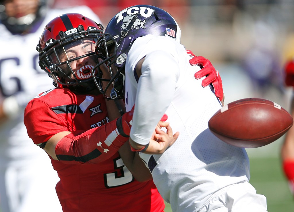 Texas Tech's Justus Parker punches the ball away from TCU's Shawn Robinson