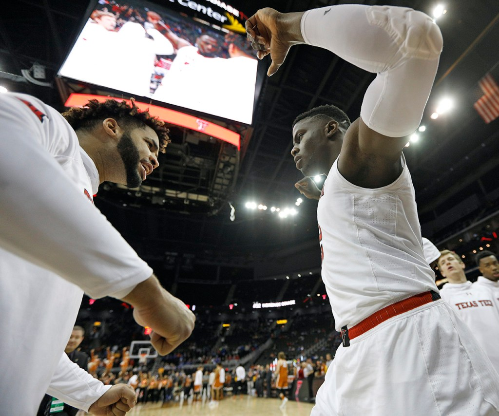Texas Tech's Norense Odiase (32) chest bumps Brandone Francis (1) as his name is called before a Big 12 basketball tournament game against Texas, Thursday, March 8, 2018, at the Sprint Center in Kansas City, Mo. [Brad Tollefson/A-J Media]