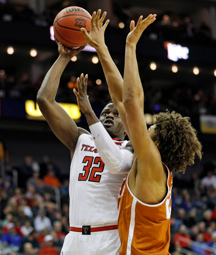 Texas Tech's Norense Odiase (32) shoots the ball around Texas' Jericho Sims (20) during a Big 12 basketball tournament game Thursday, March 8, 2018, at the Sprint Center in Kansas City, Mo. [Brad Tollefson/A-J Media]