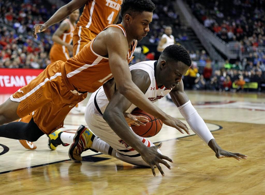 Texas' Jase Febres (13) and Texas Tech's Norense Odiase (32) dive for a loose ball during a Big 12 basketball tournament game Thursday, March 8, 2018, at the Sprint Center in Kansas City, Mo. [Brad Tollefson/A-J Media]