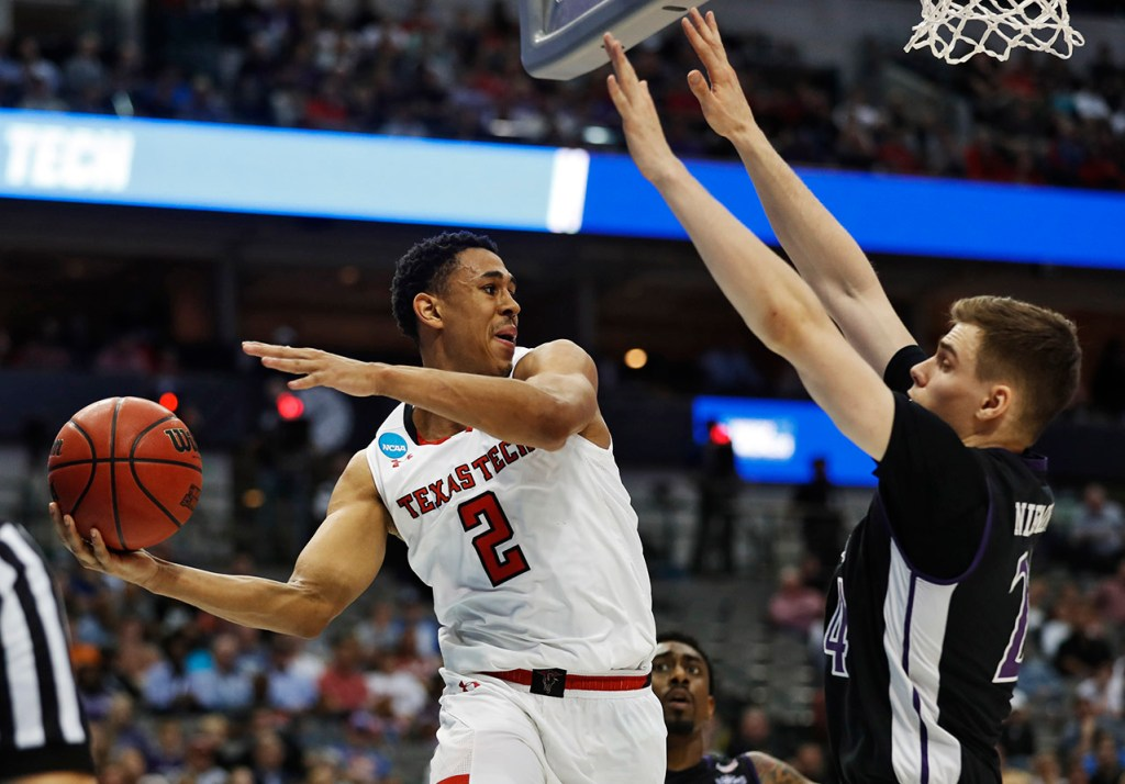 Texas Tech's Zhaire Smith (2) passes the ball around Stephen F. Austin's Samuli Nieminen (24) during an NCAA college basketball tournament first-round game Thursday, March 15, 2018, at American Airlines Center in Dallas, Texas. [Brad Tollefson/A-J Media]