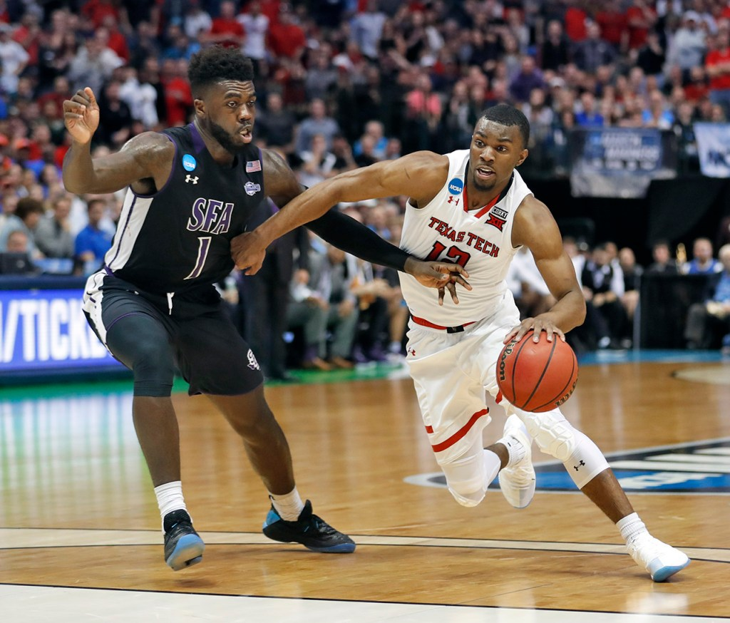 Texas Tech's Keenan Evans (12) drives the ball around Stephen F. Austin's Kevon Harris (1) during an NCAA college basketball tournament first-round game Thursday, March 15, 2018, at American Airlines Center in Dallas, Texas. [Brad Tollefson/A-J Media]