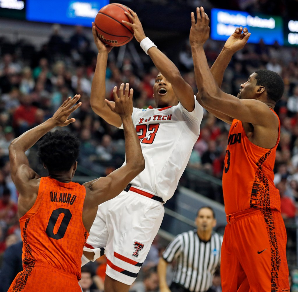 Texas Tech's Jarrett Culver (23) shoots the ball around Florida's Mike Okauru (0) and Kevarrius Hayes (13) during an NCAA college basketball tournament second-round game Saturday, March 17, 2018, at American Airlines Center in Dallas, Texas. [Brad Tollefson/A-J Media]