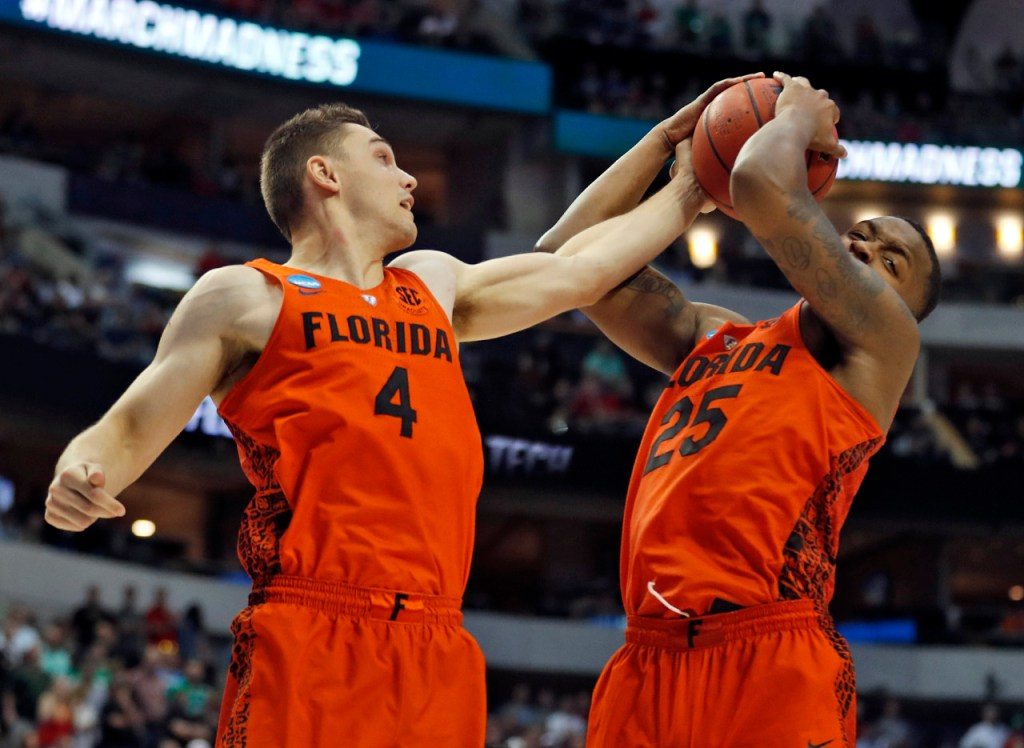 Florida's Egor Koulechov (4) and Keith Stone (25) try to rebound the ball during an NCAA college basketball tournament second-round game Saturday, March 17, 2018 at American Airlines Center in Dallas, Texas. [Brad Tollefson/A-J Media]
