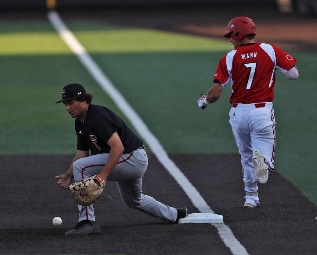 Texas Tech's Cameron Warren (11) drops the ball as Louisville's Devin Mann (7) reaches first base during an NCAA college baseball tournament regional game Sunday, June 3, 2018, in Lubbock, Texas. [Brad Tollefson/A-J Media]