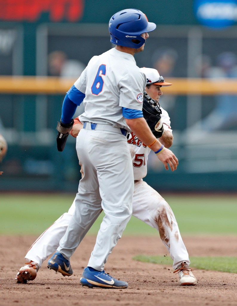 Florida's Jonathan India (6) is tagged out by Texas' Jake McKenzie (51) during a College World Series baseball game Tuesday, June 19, 2018, at TD Ameritrade Park in Omaha, Neb. [Brad Tollefson/A-J Media]