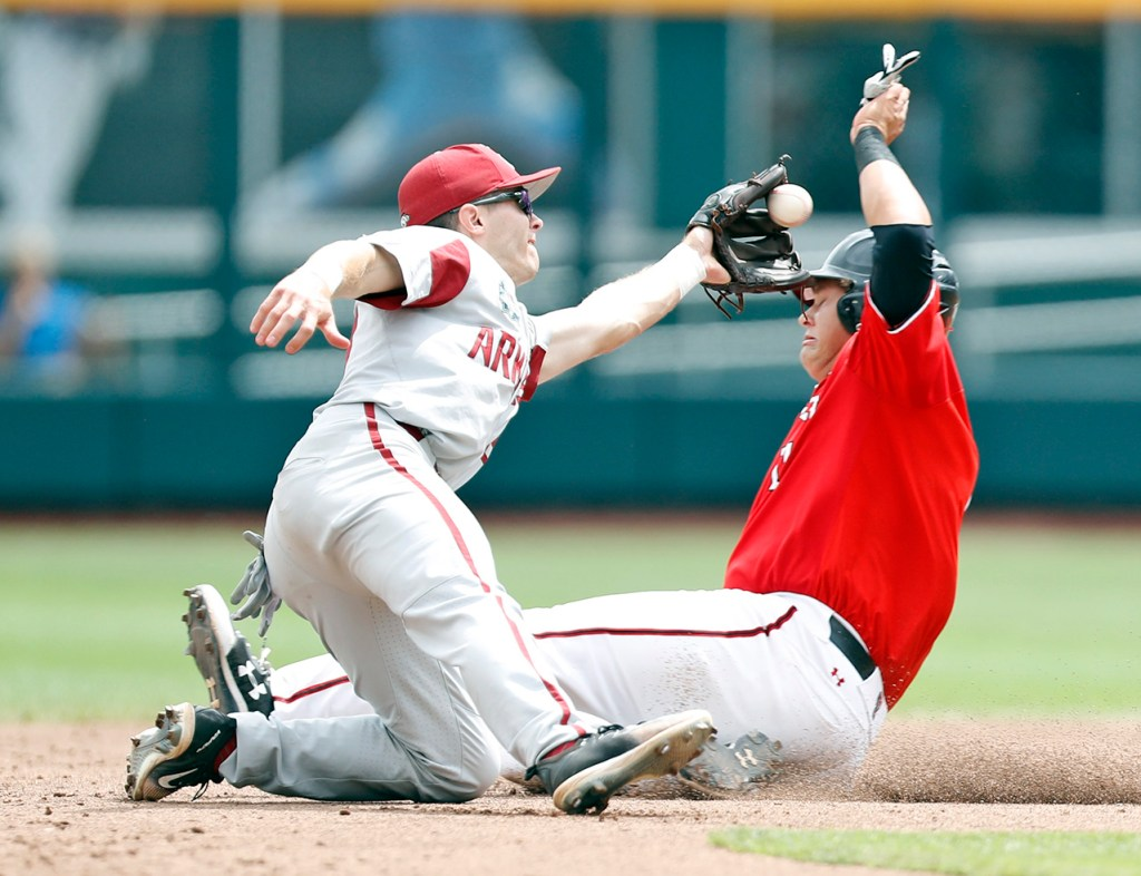 Arkansas' Carson Shaddy (20) catches the ball to tag out Texas Tech's Cameron Warren (11) as he slides into second base during a College World Series baseball game Wednesday, June 20, 2018, at TD Ameritrade Park in Omaha, Neb. [Brad Tollefson/A-J Media]