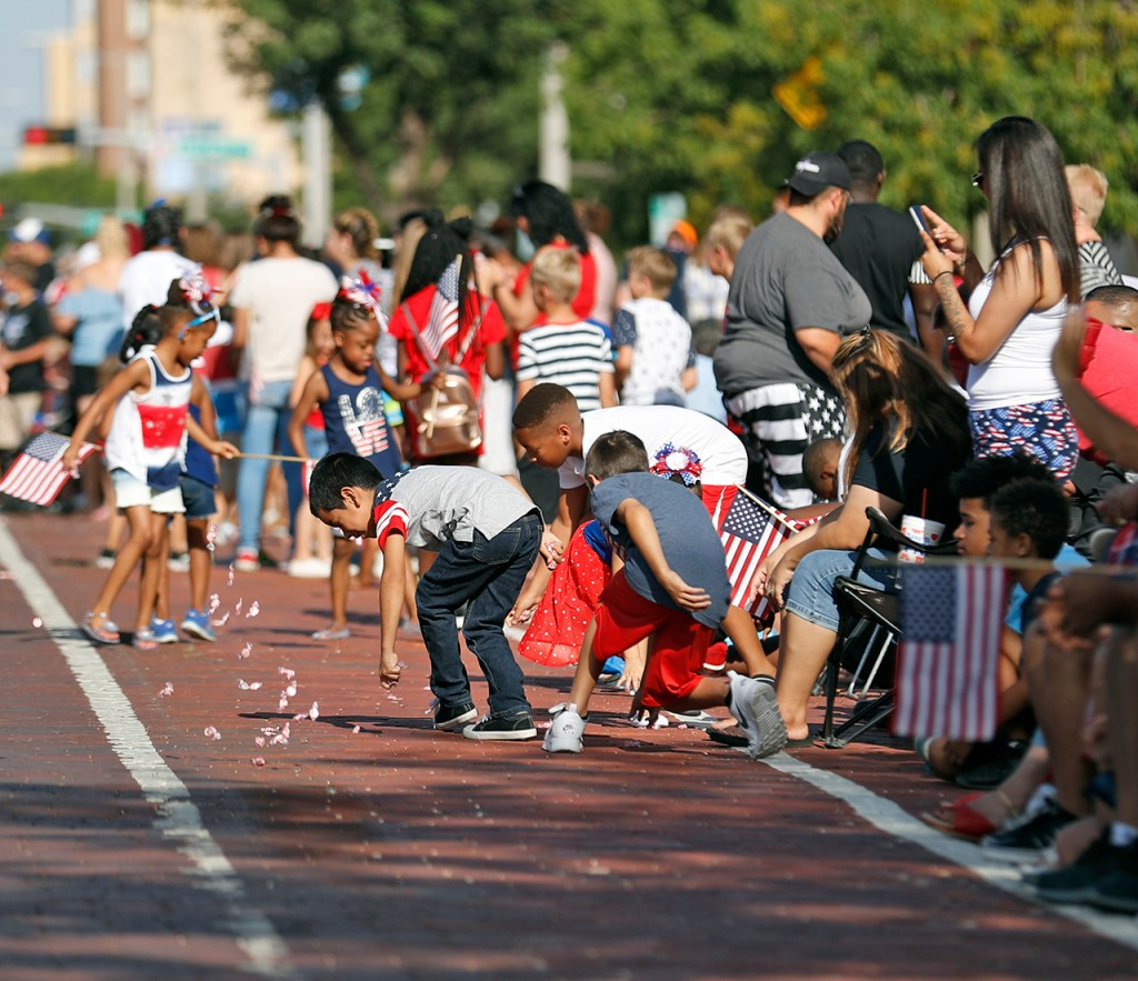 Kids pick up candy in the street during the 4th on Broadway Parade, Wednesday, July 4, 2018, in Lubbock, Texas. [Brad Tollefson/A-J Media]