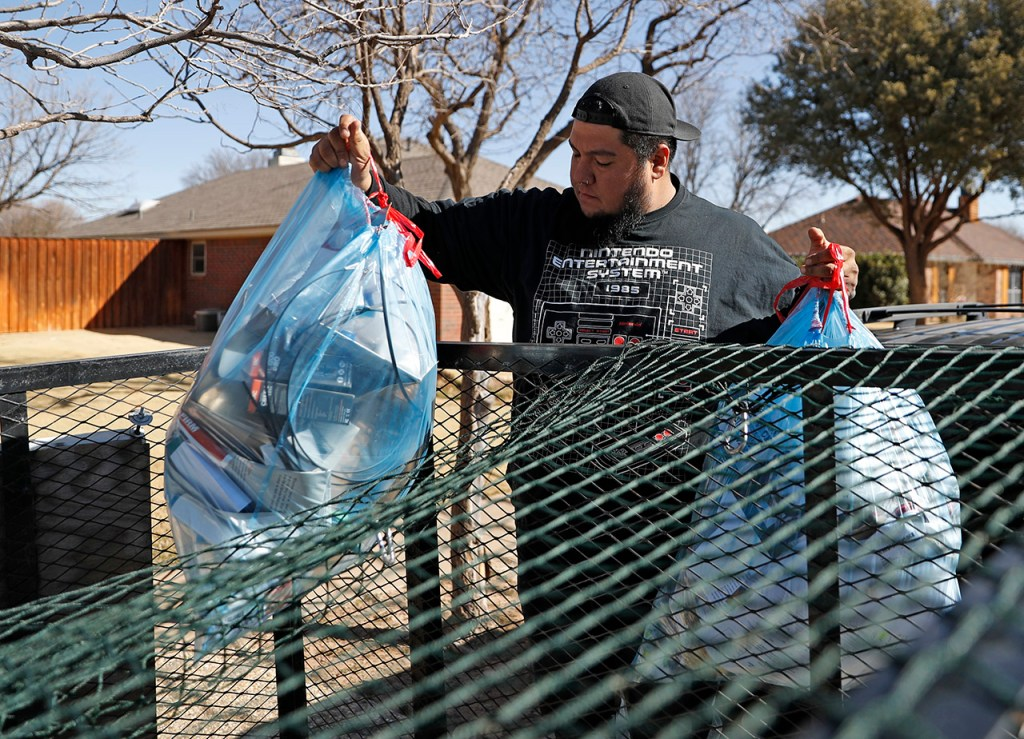 Mike Corrales, an employee with Good Earth Recycling, throws a bag of recyclables into a trailer while picking them up from a customer Wednesday, Feb. 20, 2019, in Lubbock, Texas. [Brad Tollefson/A-J Media]