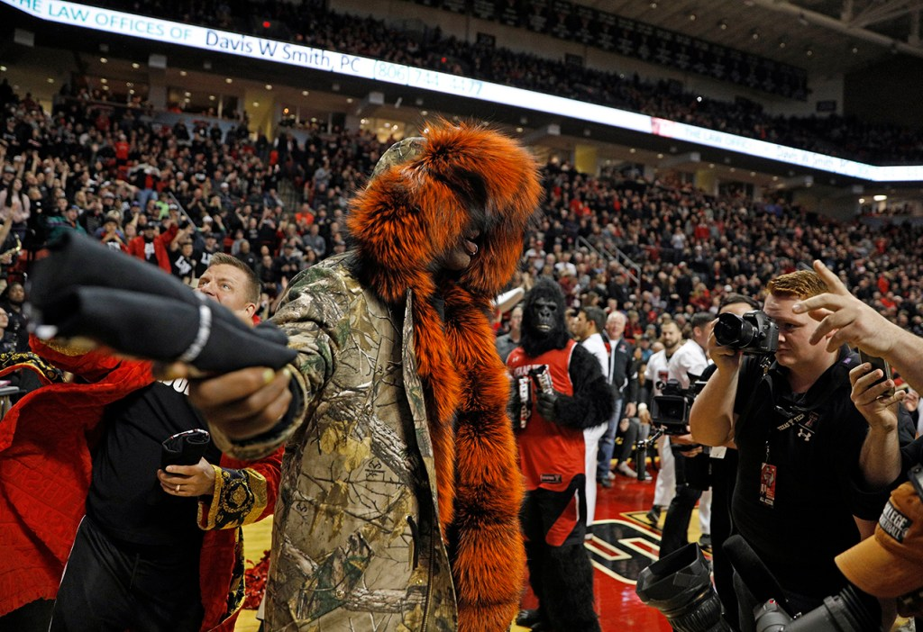 Dennis Rodman throws a t-shirt into a crowd of Texas Tech students during the first half of an NCAA college basketball game against Texas, Monday, March 4, 2019, in Lubbock, Texas. (AP Photo/Brad Tollefson)