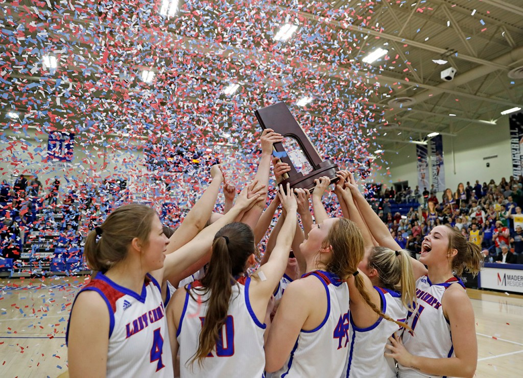 Lubbock Christian players celebrate with the trophy after the NCAA south central regional final against Angelo State, Tuesday, March 19, 2019, at Rip Griffin Center in Lubbock, Texas. [Brad Tollefson/A-J Media]